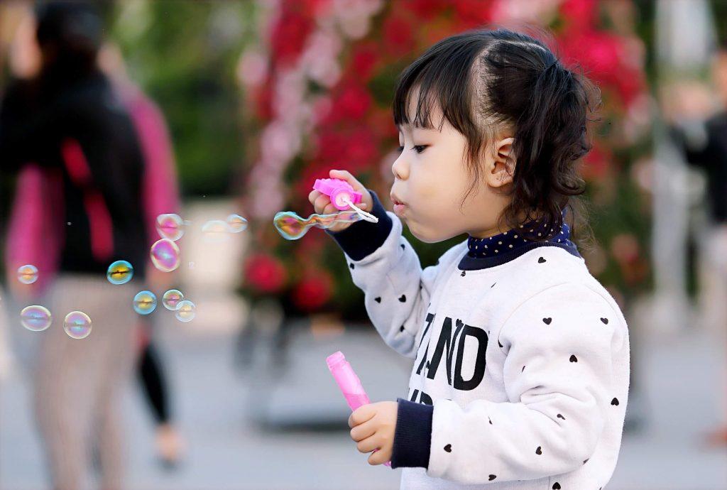 Criança asiática brincando com bolinhas de sabão