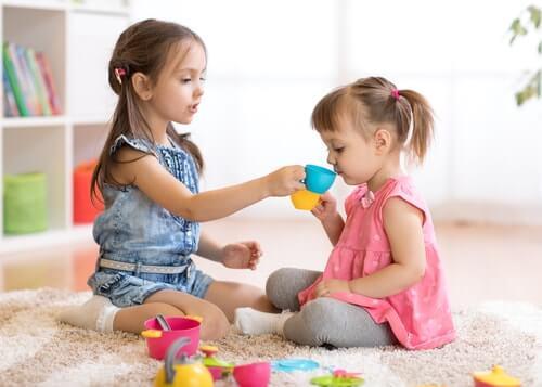 Duas meninas brincando de tomar chá com brinquedos coloridos