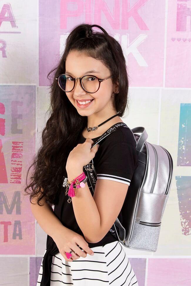 Menina Pampili com mochila prata e blusa preta