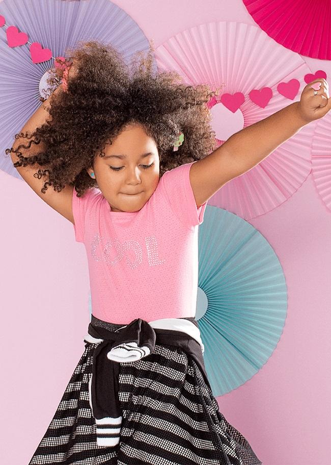 Menina brincando com blusinha rosa e saia listrada