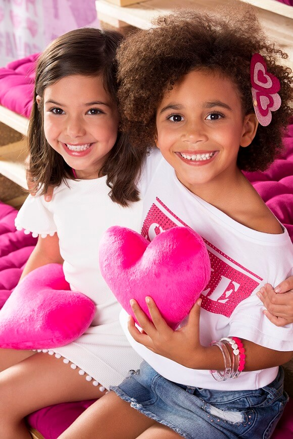 Meninas Pampili abraçadas com coração rosa de pelúcia