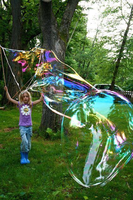 Menina brincando com bolha de sabão com varetas