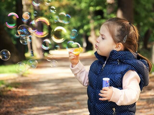 Menina brincando com bolha de sabão
