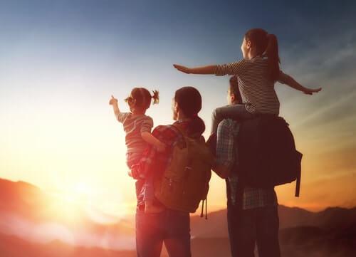 Família mochileira apreciando o pôr do sol