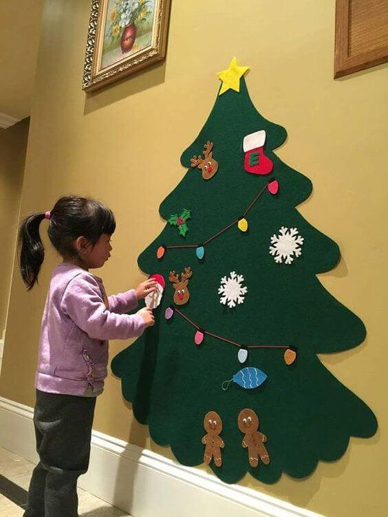 Menina decorando árvore de natal de feltro