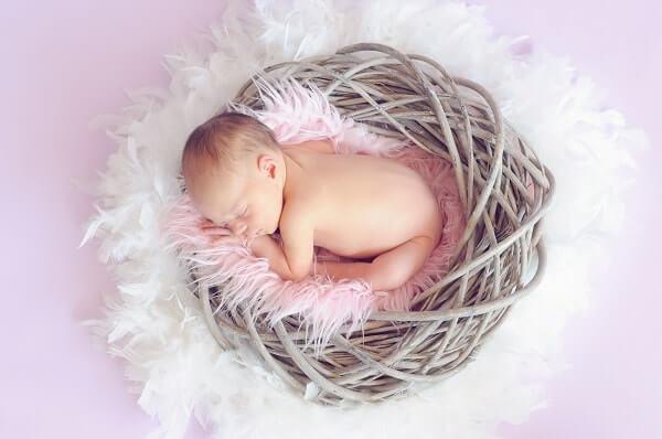 Bebê dormindo em um cesto de vime
